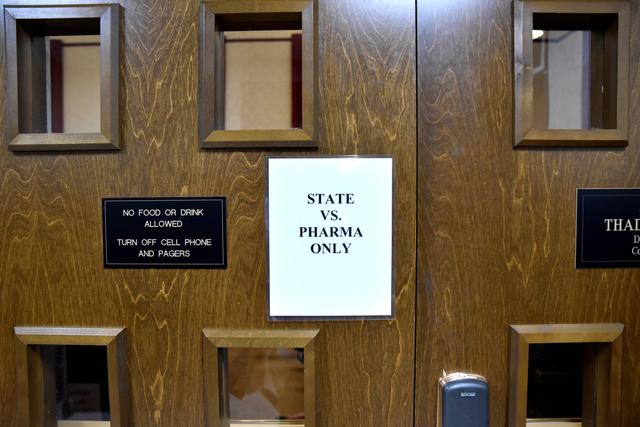 A sign is seen on the outside of the courtroom on the first day of a trial of Johnson & Johnson over claims they engaged in deceptive marketing that contributed to the national opioid epidemic in Norman, Oklahoma, U.S. May 28, 2019.  REUTERS/Nick Oxford