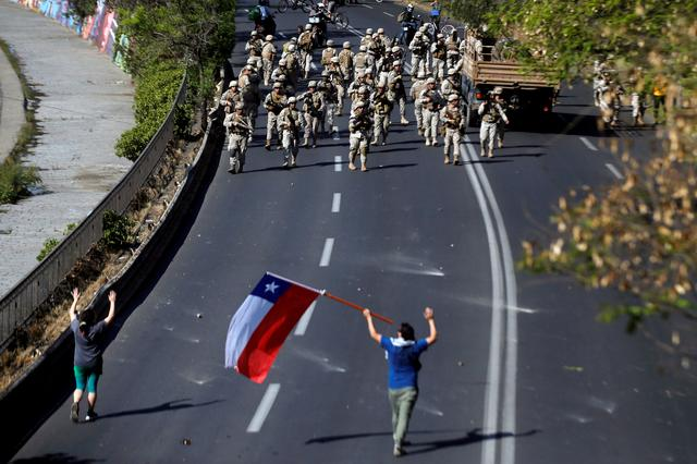 FILE PHOTO: Chilean soldiers gather near demonstrators, one of whom holds a Chilean flag, during a protest against Chile's state economic model in Santiago, Chile, October 20, 2019. REUTERS/Edgard Garrido/File Photo