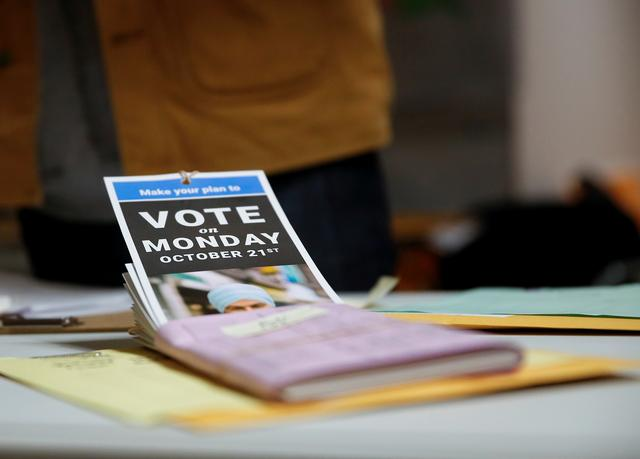 Voting information pamphlets sit on a table as New Democratic Party (NDP) leader Jagmeet Singh helps sort documents at the NDP election office on Election Day in Burnaby, British Columbia, Canada October 21, 2019.  REUTERS/Lindsey Wasson