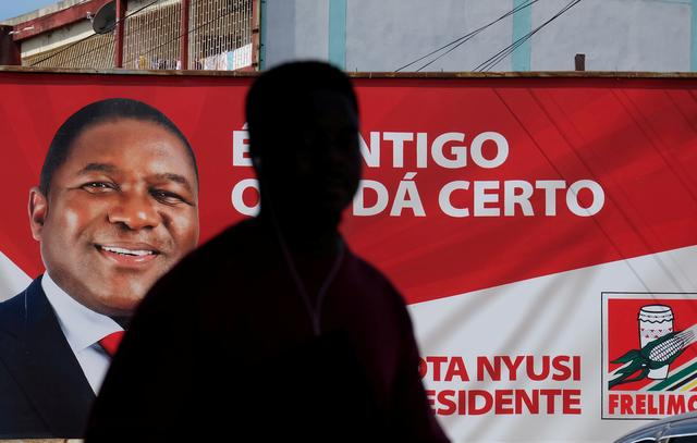 FILE PHOTO: A local walks past a billboard with a picture of Mozambique's president and leader of the Frelimo Party, Filipe Nyusi, ahead of Tuesday's provincial and legislative elections, in Maputo, Mozambique, October 11, 2019. REUTERS/Grant Lee Neuenburg/File Photo