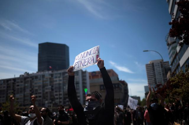 """A demonstrator holds a sign reading """"Pinera, resign"""" during a protest against high living costs, in Concepcion, Chile October 21, 2019. REUTERS/Juan Gonzalez"""