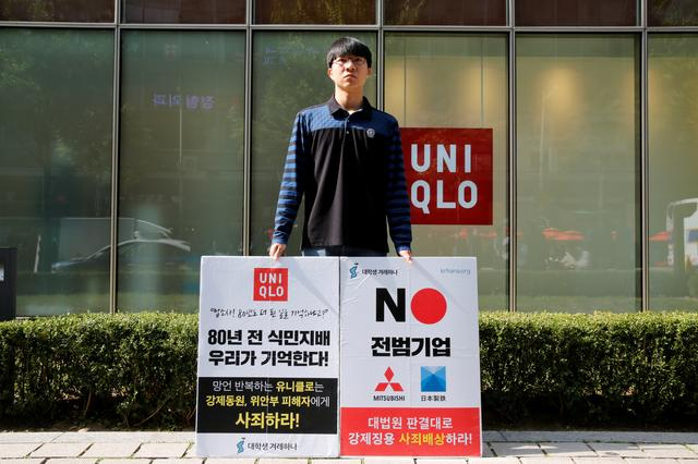 """A university student Bang Seulkichan stands with banners as a protest against recent released Uniqlo commercial in front of a Uniqlo store in Seoul, South Korea, October 22, 2019. The banner reads """"Colonial rule 80 years ago – we remember!""""    REUTERS/Heo Ran"""