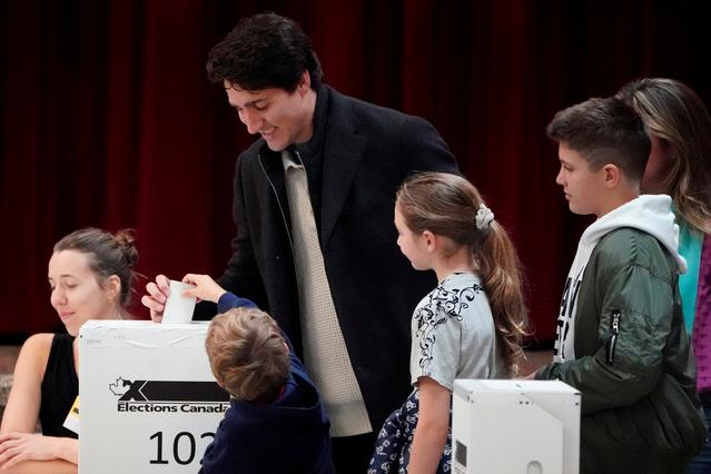 Justin Trudeau, with his family, puts his ballot for today's election in the ballot box in the Papineau area of Montreal, Quebec, Canada, October 21, 2019. REUTERS/Carlo Allegri