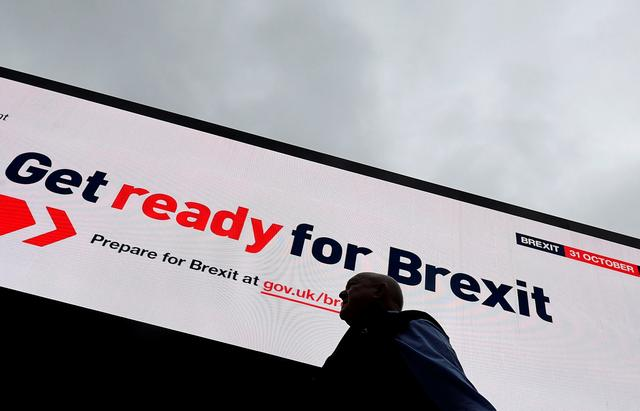 FILE PHOTO: A man passes an electronic billboard displaying a British government Brexit information awareness campaign advertisement in London, Britain, September 11, 2019. REUTERS/Toby Melville/File Photo