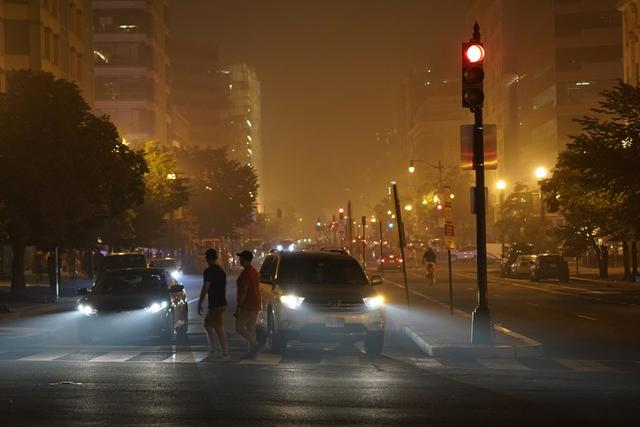 FILE PHOTO: Traffic and pedestrians along a smoke-filled street after fireworks during Fourth of July Independence Day celebrations, in downtown Washington, D.C., U.S., July 4, 2019. REUTERS/Joshua Roberts/File Photo
