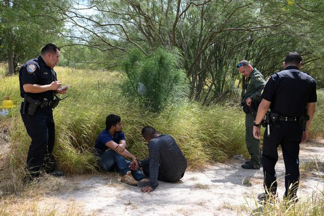 FILE PHOTO: Migrant men sit on the ground after being detained by law enforcement for illegally crossing the Rio Grande and attempting to evade capture in Hidalgo, Texas, U.S., August 23, 2019. REUTERS/Loren Elliott/File Photo