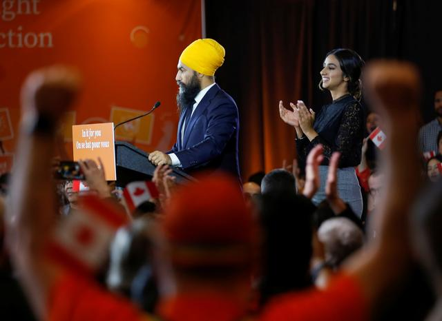 New Democratic Party leader Jagmeet Singh speaks to supporters after being re-elected in Burnaby South as wife Gurkiran Kaur Sidhu claps at an NDP election night party in Burnaby, British Columbia, Canada, October 21, 2019.  REUTERS/Lindsey Wasson