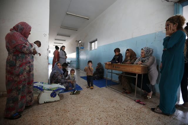 Displaced Kurdish and Arab women, who fled from violence after a Turkish offensive in northeastern Syria, sit with their children at a public school used as shelter where they live now in Hasakah, Syria, October 22, 2019. REUTERS/Muhammad Hamed