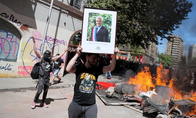 A demonstrator holds a picture of Chilean President Sebastian Pinera during a protest against Chile's state economic model, in Santiago, Chile October 22, 2019. REUTERS/Ivan Alvarado NO RESALES. NO ARCHIVES