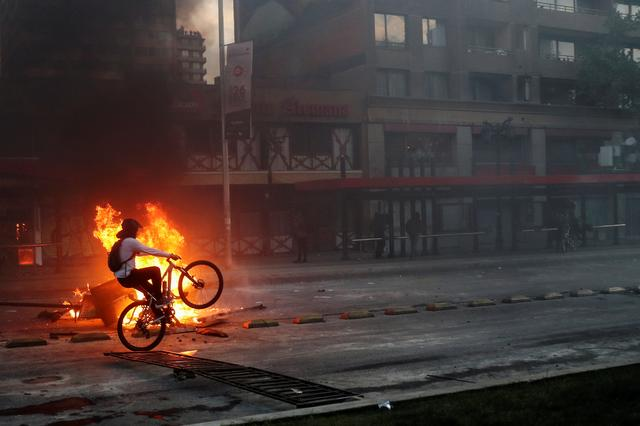 A demonstrator rides a bicycle past an improvised bonfire during a protest against the increase in subway ticket prices in Santiago, October 19. REUTERS/Ivan Alvarado