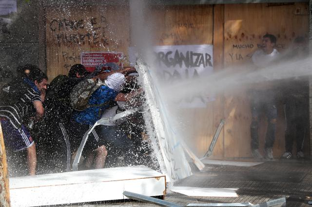 Demonstrators take cover as they are sprayed by security forces with a water cannon during a protest against Chile's state economic model in Santiago, Chile October 22, 2019. REUTERS/Ivan Alvarado