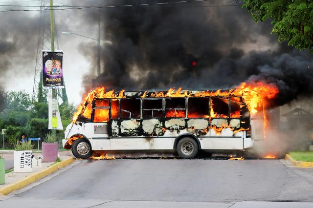 """FILE PHOTO: A burning bus, set alight by cartel gunmen to block a road, is pictured during clashes with federal forces following the detention of Ovidio Guzman, son of drug kingpin Joaquin """"El Chapo"""" Guzman, in Culiacan, Sinaloa state, Mexico October 17, 2019. REUTERS/Jesus Bustamante"""