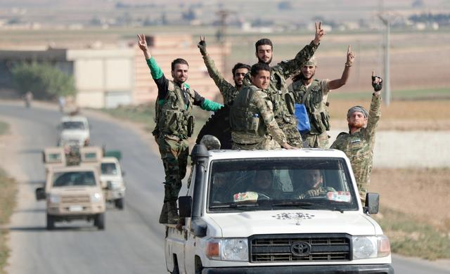 Turkey-backed Syrian rebel fighters gesture as they ride on a vehicle near the border town of Tal Abyad, Syria, October 22, 2019. REUTERS/Khalil Ashawi     TP