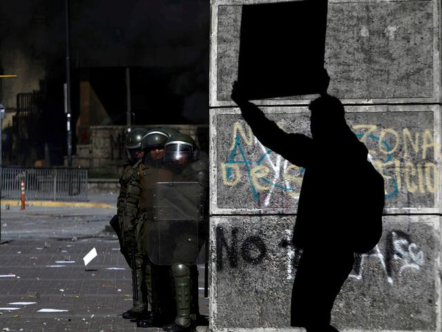 A demonstrator holding a sign walks in front of security forces as protests against high living costs continue, in Concepcion, Chile October 22, 2019. REUTERS/Juan Gonzalez