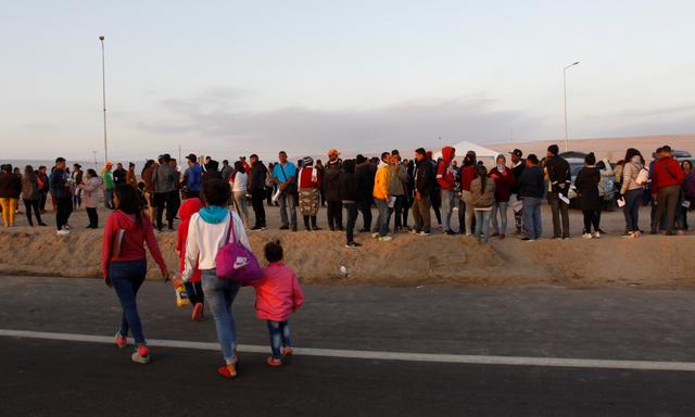 FILE PHOTO: Venezuelan citizens line up at the Chacalluta border crossing are between Chile and Peru, in Arica, Chile, June 24, 2019. REUTERS/Stringer/File Photo