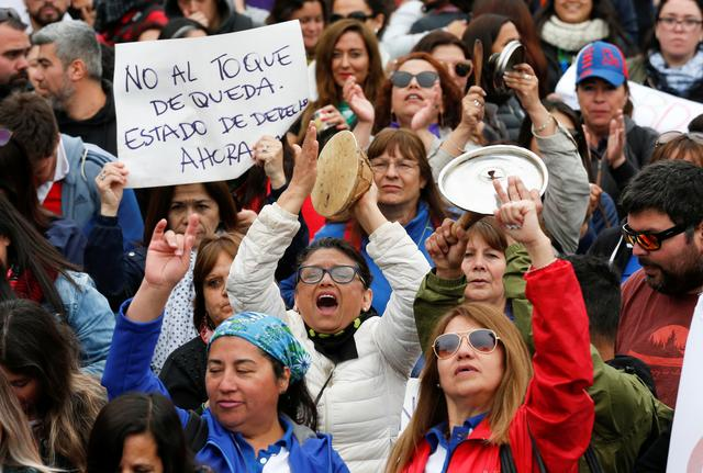 """People take part in a rally in Valparaiso, Chile October 23, 2019. The placard reads: """"No to the curfew, rule of law now"""". REUTERS/Rodrigo Garrido"""