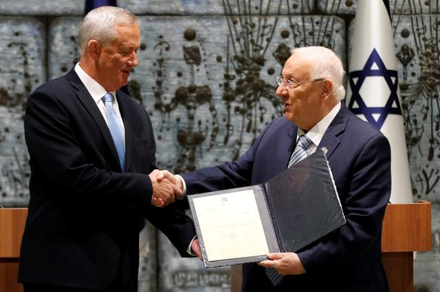Israeli President Reuven Rivlin gives Benny Gantz, leader of Blue and White party, a file during a nomination ceremony at the President's residency in Jerusalem October 23, 2019 REUTERS/ Ronen Zvulun
