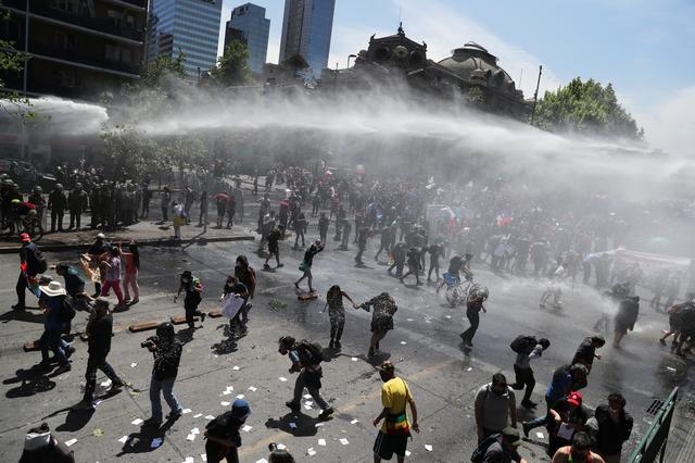 Demonstrators are sprayed by security forces with water cannons during a protest against Chile's state economic model in Santiago, Chile October 23, 2019. REUTERS/Ivan Alvarado
