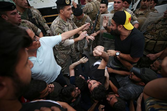 Lebanese army soldiers confront with demonstrators in an attempt to open a blocked road during ongoing anti-government protests in the port city of Sidon, Lebanon October 23, 2019. REUTERS/Ali Hashisho