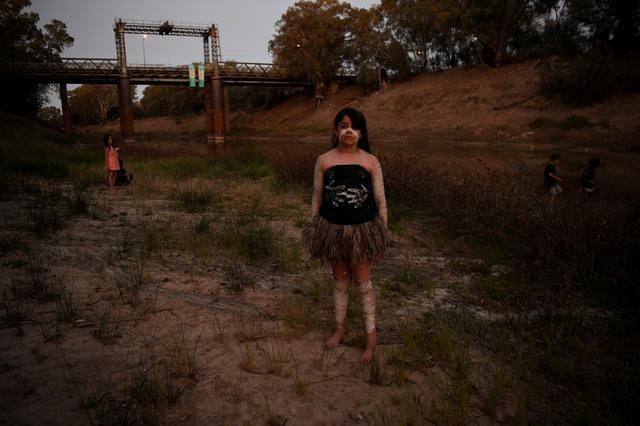 """Ngiyaampaa girl Punta Williams poses for photographs on the dry riverbed before performing at Yaama Ngunna Baaka Corroboree Festival on the banks of the Darling River in Wilcannia, New South Wales, Australia, October 1, 2019. Recently, Aboriginal communities held special festivals along the river """"to heal the Barka"""". Ochre-painted dancers performed around fires at dusk, revering the river but also seeking to draw attention to its plight. REUTERS/Tracey Nearmy"""