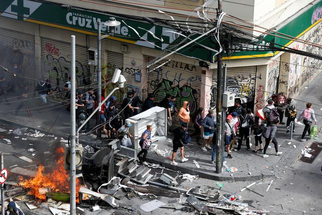 People walk towards a pharmacy during clashes in Valparaiso, Chile October 23, 2019. REUTERS/Rodrigo Garrido