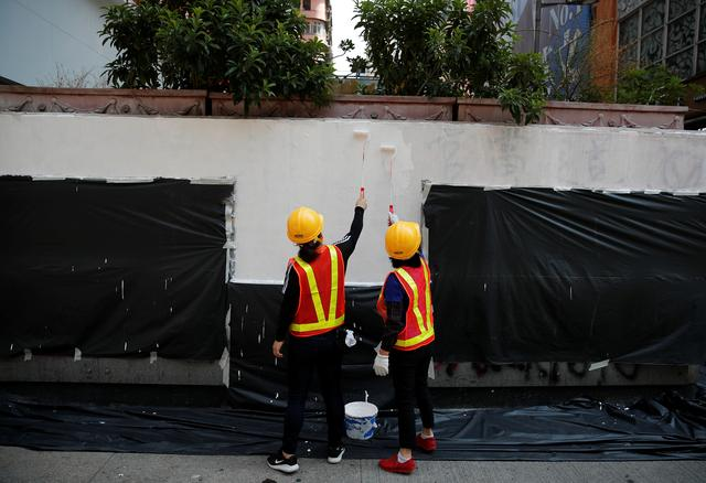 Workers paint to cover words which were written during Sunday's anti-government protest on the walls of a bank branch in Hong Kong, China, October 23, 2019. REUTERS/Umit Bektas