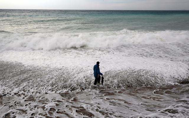 FILE PHOTO: A man walks on the beach in Nice as storms and heavy rain lashed through southern France, October 23, 2019.  REUTERS/Eric Gaillard/File Photo
