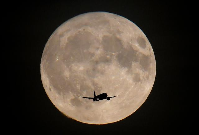 FILE PHOTO: A passenger plane is seen with the full moon behind as it begins its final landing approach to Heathrow Airport in London, Britain, September 24, 2018. REUTERS/Toby Melville