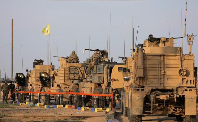 FILE PHOTO: American soldiers stand near military trucks, at al-Omar oil field in Deir Al Zor, Syria March 23, 2019. REUTERS/Rodi Said/File Photo