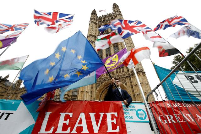 FILE PHOTO: An anti-Brexit protester waves an EU flag outside the Houses ofParliamentin London, Britain, October 25, 2019. REUTERS/Henry Nicholls/File Photo