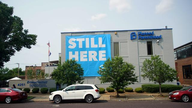 "FILE PHOTO: A banner stating ""STILL HERE"" hangs on the side of the Planned Parenthood Building after a judge granted a temporary restraining order on the closing of Missouri's sole remaining Planned Parenthood clinic in St. Louis, Missouri, U.S. May 31, 2019.  REUTERS/Lawrence Bryant/File Photo"