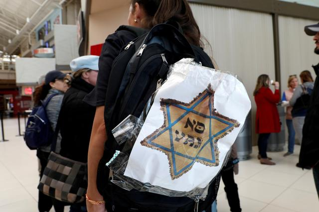 "FILE PHOTO: A woman opposed to childhood vaccinations wears a ""No Vax"" sign on her backpack as she takes part in a demonstration after officials in Rockland County, a New York City suburb, banned children not vaccinated against measles from public spaces, in West Nyack, New York, U.S. March 28, 2019. REUTERS/Mike Segar/File Photo"