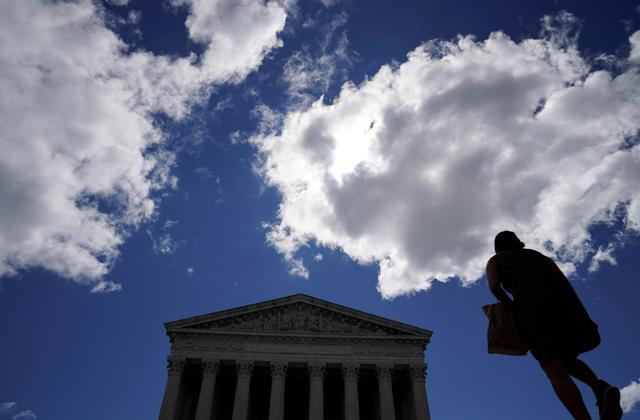 FILE PHOTO: A woman walks up the steps to the U.S. Supreme Court in Washington, U.S., June 21, 2019.  REUTERS/Kevin Lamarque/File Photo