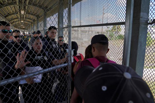 FILE PHOTO: U.S. Customs and Border Protection agents open the gates to the port of entry so that asylum seekers who had a court date that day can either attend it or reschedule it, as a group of migrants, who returned to Mexico to await their U.S. asylum hearing, block the Puerta Mexico international border crossing bridge to demand a speedier asylum process in Matamoros, Mexico October 10, 2019. REUTERS/Veronica G. Cardenas