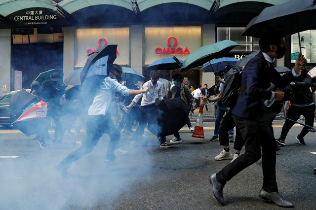 Office workers run away from tear gas as they attend a flash mob anti-government protest at the financial Central district in Hong Kong, China, November 11, 2019. REUTERS/Tyrone Siu