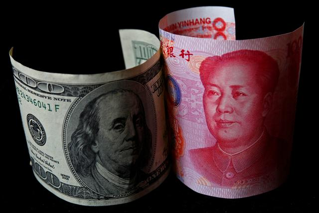 FILE PHOTO: A 100 yuan banknote (R) is placed next to a $100 banknote in this picture illustration taken in Beijing November 7, 2010. REUTERS/Petar Kujundzic/File Photo