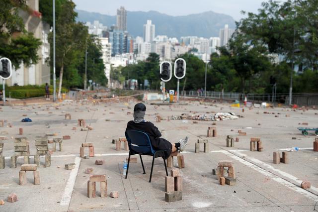 A protester sits amid a road block outside City University in Kowloon Tong, Hong Kong, China November 12, 2019.  REUTERS/Thomas Peter