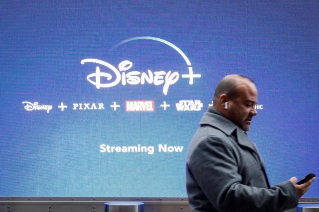 A man looks at his phone as he passes by a screen advertising Walt Disney's streaming service Disney+ in New York City, U.S., November 12, 2019. REUTERS/Brendan McDermid