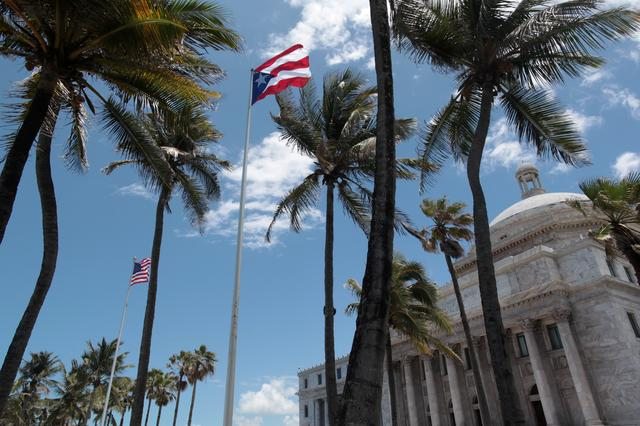 FILE PHOTO: The flags of the U.S. and Puerto Rico fly outside the Capitol building in San Juan, Puerto Rico May 4, 2017. REUTERS/ Alvin Baez/File Photo