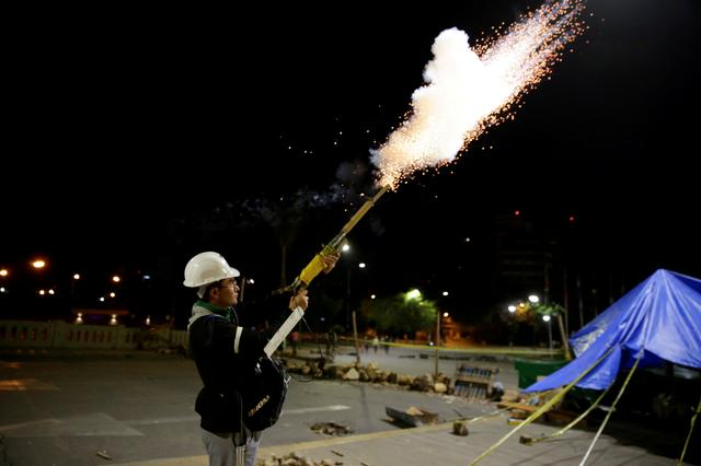 """A member of Youth Resistance """"Cochala"""" set off fireworks to celebrate after Bolivian Senator Jeanine Anez became interim president, following Bolivia's former President Evo Morales' departure from the country, in Cochabanba, Bolivia November 12, 2019. REUTERS/David Mercado"""