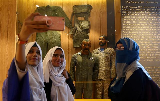 Students take selfies with a mannequin, representing Indian pilot Wing Commander Abhinandan Varthaman, after his Mig-21 fighter aircraft was shot down by Pakistan Air Force on February 27, 2019, at a gallery 'Operation Swift Retort' at the Pakistan Air Force (PAF) Museum in Karachi, Pakistan November 13, 2019. REUTERS/Imran Ali