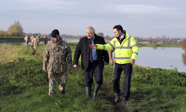 Prime Minister Boris Johnson walks with Lt Col Tom Robinson from the Light Dragoons and Oliver Harmar, Yorkshire Area Director of the Environment Agency, following recent flooding in Stainforth, Doncaster, Britain November 13, 2019. Danny Lawson/Pool via REUTERS