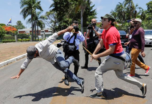 A supporter of Venezuela's President Nicolas Maduro fights with an opposition leader Juan Guaido's supporter outside Venezuelan embassy in Brasilia, Brazil, November 13, 2019. REUTERS/Sergio Moraes