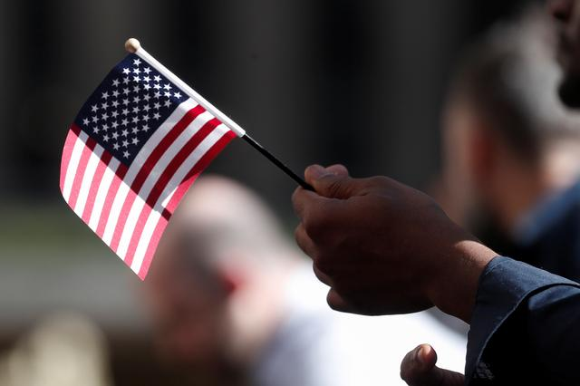 FILE PHOTO: A citizenship candidate holds a flag during the U.S. Citizenship and Immigration Services (USCIS) naturalization ceremony at Rockefeller Plaza in New York City, U.S., September 17, 2019. REUTERS/Shannon Stapleton