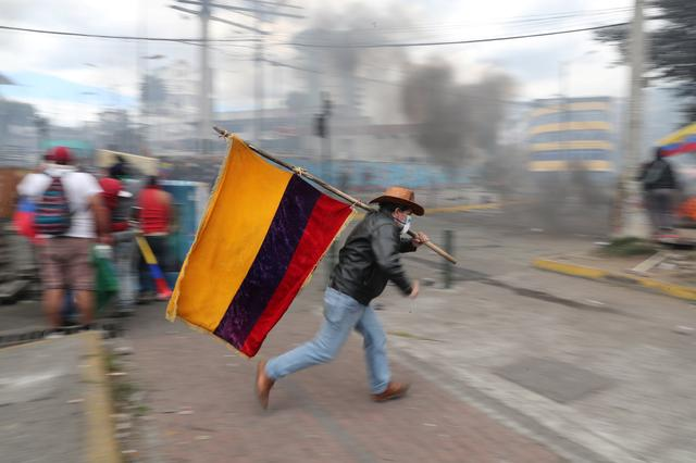 FILE PHOTO: A demonstrator runs while holding an Ecuadorian flag during a protest against Ecuador's President Lenin Moreno's austerity measures in Quito, Ecuador October 12, 2019. Picture taken October 12, 2019. REUTERS/Ivan Alvarado