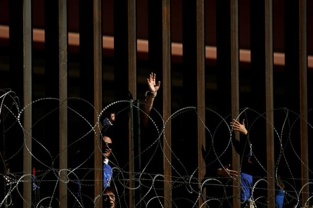 """FILE PHOTO: People wave from behind the border fence in El Paso, Texas, U.S., before a brief reunification meeting for relatives separated by deportation and immigration, called """"Hugs, Not Walls,"""" as pictured from Ciudad Juarez, Mexico October 26, 2019. REUTERS/Jose Luis Gonzalez"""
