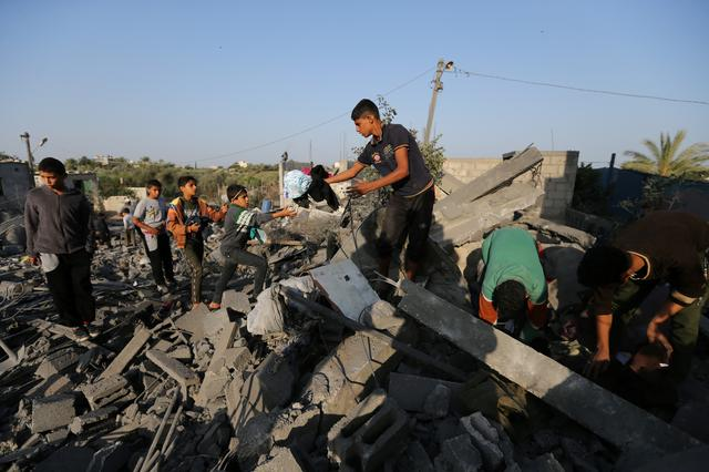 Palestinians collect belongings from a house destroyed in an Israeli air strike in the southern Gaza Strip November 14, 2019. REUTERS/Ibraheem Abu Mustafa