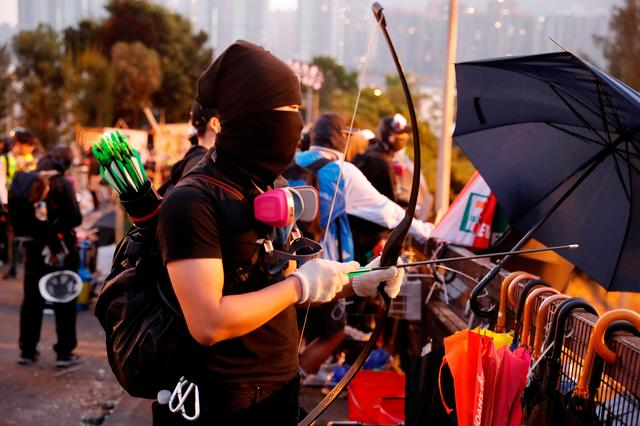 FILE PHOTO: An anti-government protester holds a bow as he stands at a makeshift gate during a standoff with riot police at the Chinese University of Hong Kong, Hong Kong, China November 14, 2019. REUTERS/Tyrone Siu/File Photo