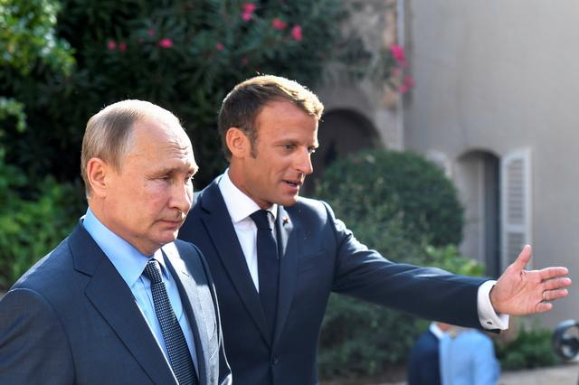FILE PHOTO: French President Emmanuel Macron welcomes Russia's President Vladimir Putin, at his summer retreat of the Bregancon fortress on the Mediterranean coast, near the village of Bormes-les-Mimosas, southern France, on August 19, 2019. Gerard Julien/Pool via REUTERS/File Photo