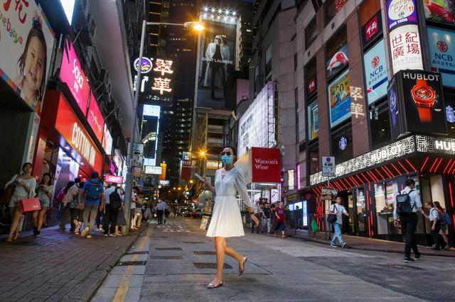 FILE PHOTO: A woman crosses a street in the Central business district in Hong Kong, China August 22, 2019.  REUTERS/Thomas Peter/File Photo
